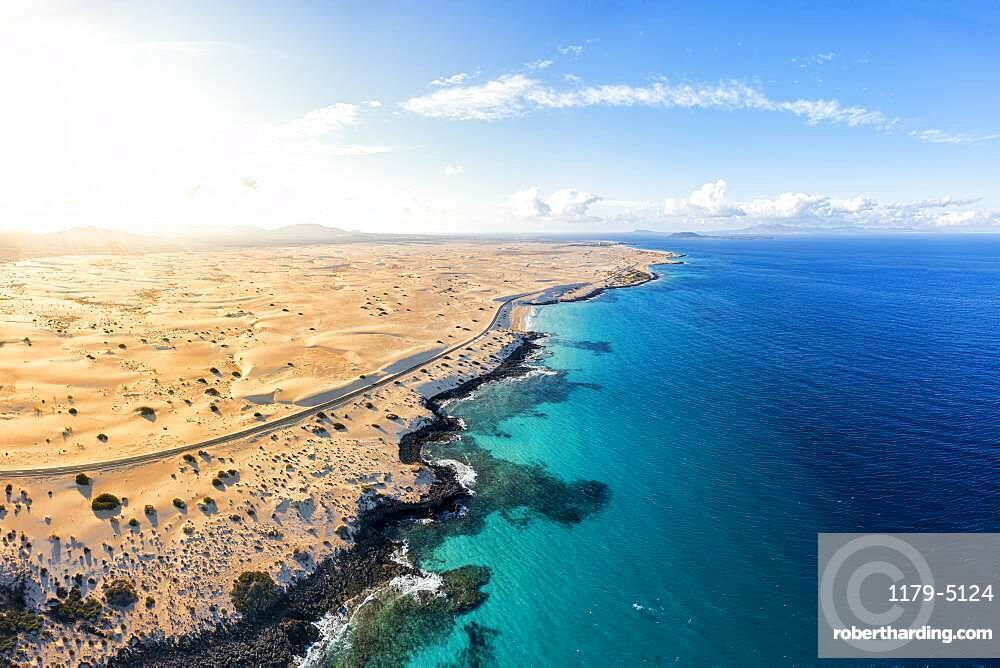 Aerial view of empty road beside the crystal turquoise ocean and sand dunes, Corralejo, Fuerteventura, Canary Islands, Spain
