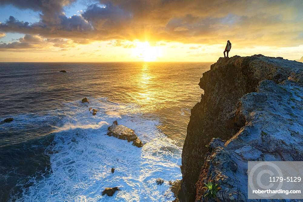 One man watching sunrise over the ocean waves from cliffs, Madeira island, Portugal
