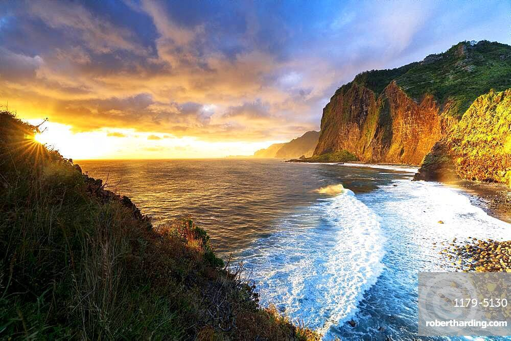 Scenic sky at dawn over waves crashing on cliffs, Madeira island, Portugal