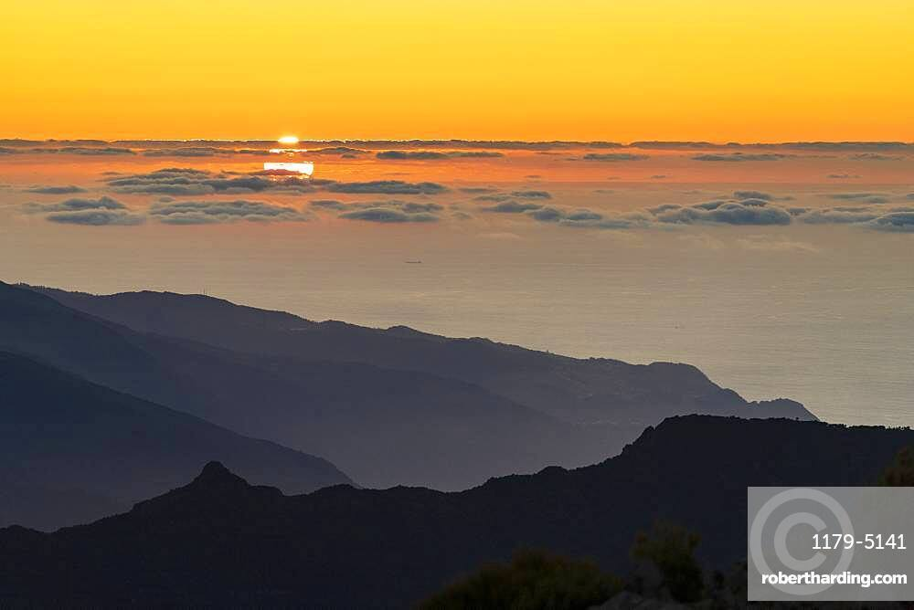 Burning sky at sunset over the Atlantic Ocean and silhouettes of mountains from Pico Ruivo peak, Madeira, Portugal