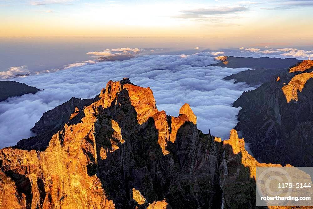 Clouds surrounding the rocky peak of Pico das Torres lit by sunset, Madeira island, Portugal