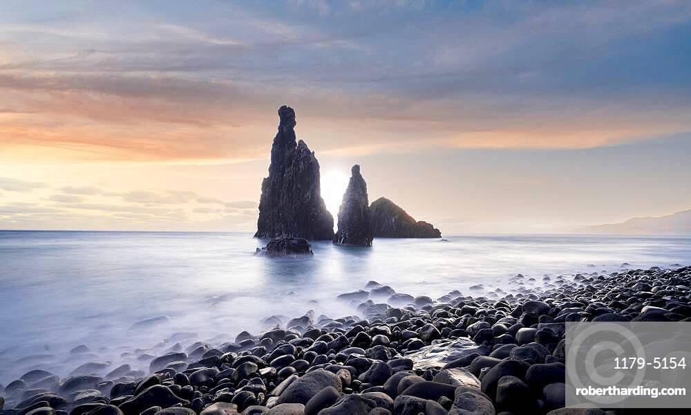 Waves crashing on volcanic stone beach and sea stacks Ilheus da Rib and Ribeira da Janela at sunrise, Madeira island, Portugal