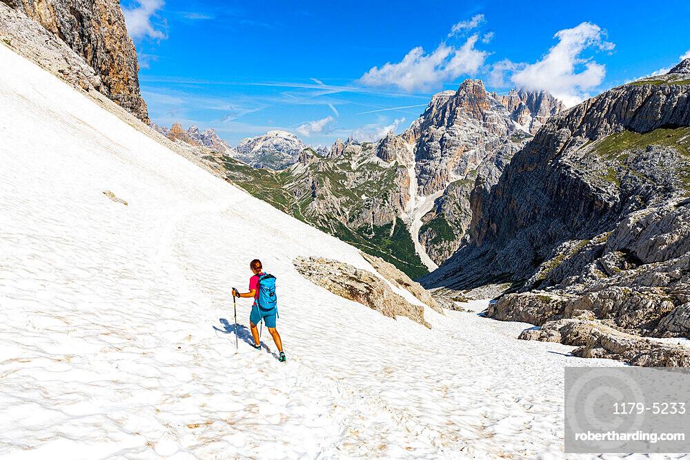 Hiker woman walking on snowy mountain ridge on path to Rifugio Locatelli hut, Sesto Dolomites, South Tyrol, Italy