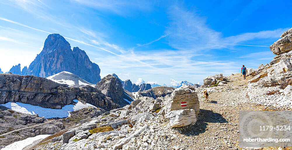 Hiker woman with dog walking on path to the majestic mountain Croda dei Toni in summer, Sesto Dolomites, South Tyrol, Italy