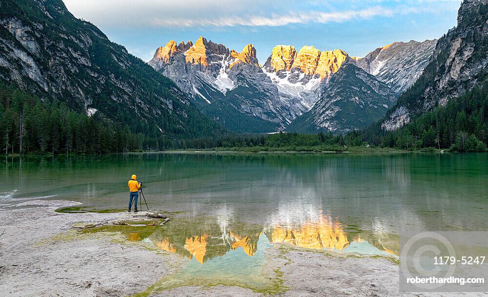 Photographer with tripod admiring the Dolomites at dawn from lake Landro, Dolomites, Bolzano province, South Tyrol, Italy