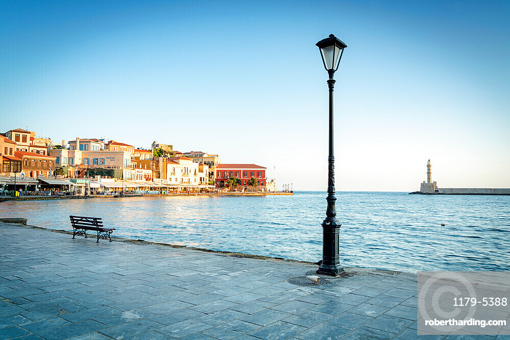 Old lantern in the Venetian harbour of Chania with lighthouse on background, Crete, Greece
