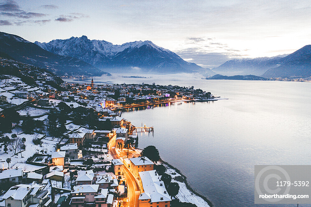 Sunrise over the traditional houses of Domaso covered with snow at Christmas time, Lake Como, province of Como, Lombardy, Italy