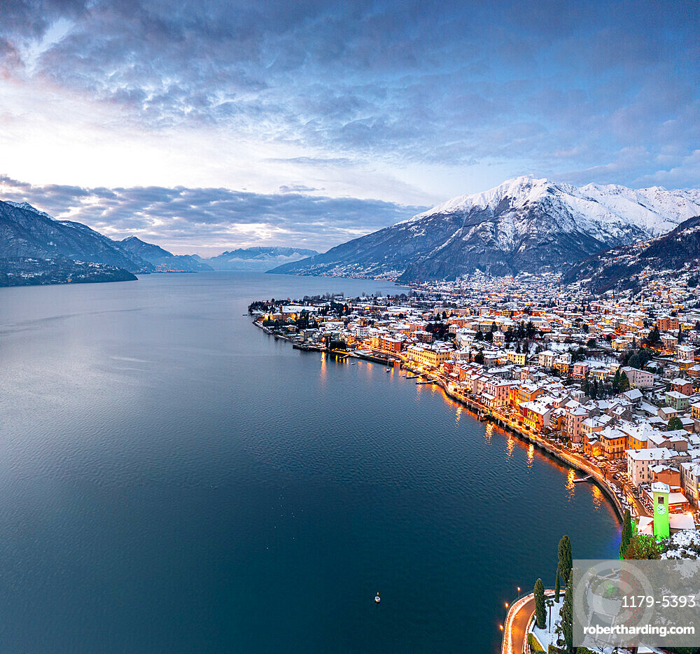 Winter sunrise over the illuminated lakeside town of Gravedona and snowy peaks, Lake Como, province of Como, Lombardy, Italy