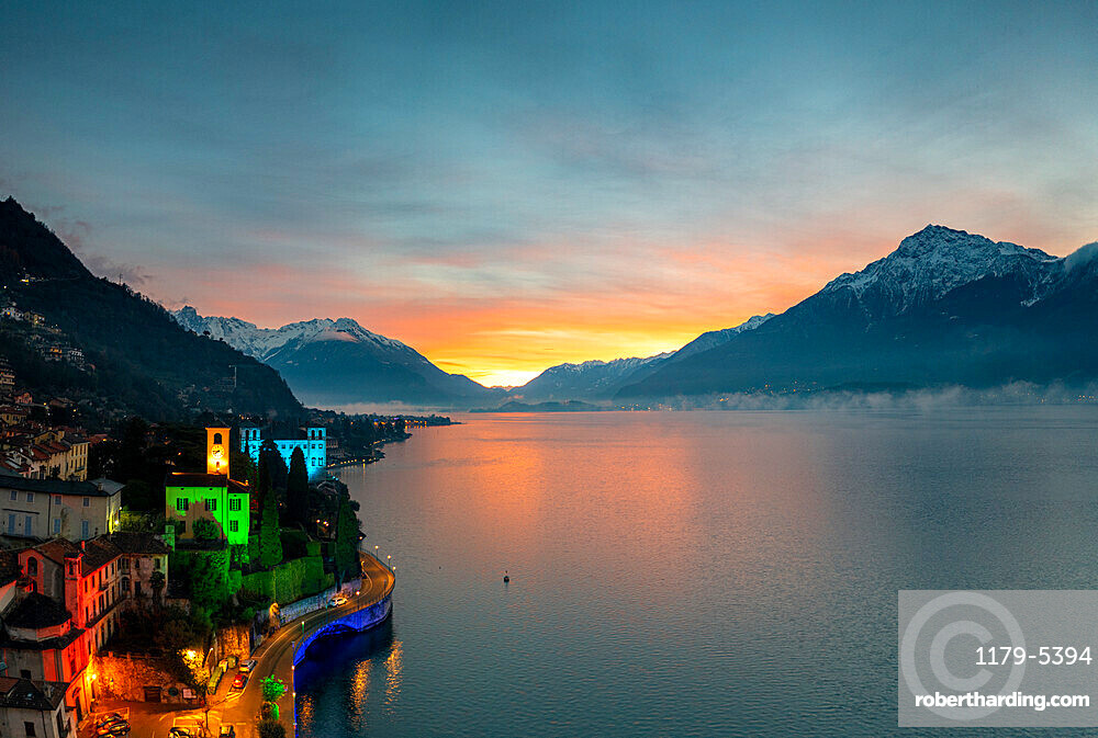 Christmas lights decorating the old bell tower and houses in Gravedona during sunrise, Lake Como, Lombardy, Italy