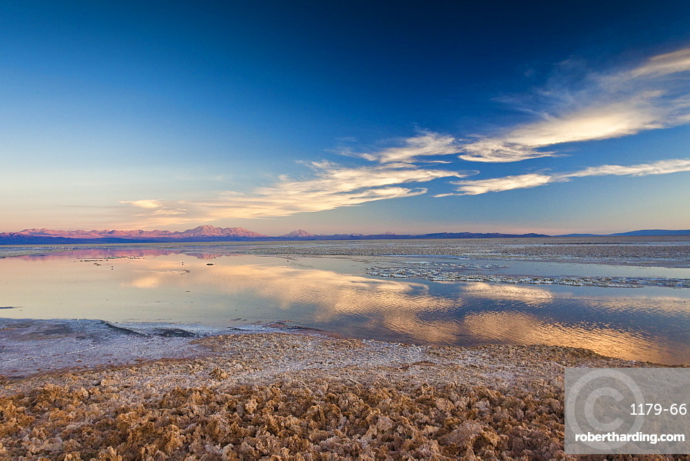 Pink clouds reflecting in a pool by the Chaxa Lagoon in the Atacama Desert, Chile, South America