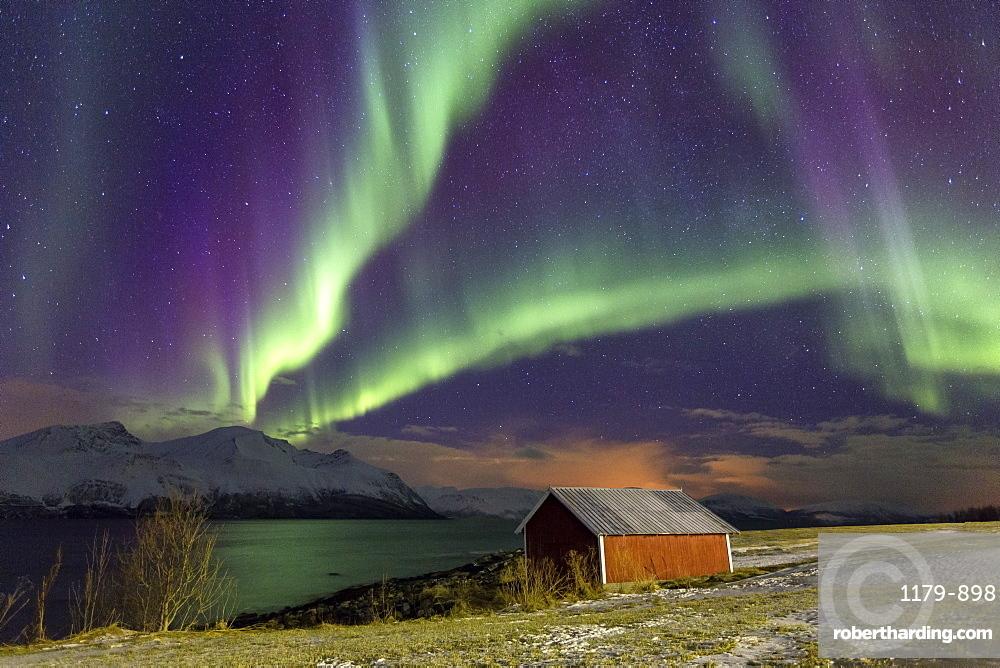 Northern Lights illuminates the wooden cabin at Svensby, Lyngen Alps, Troms, Lapland, Norway, Scandinavia, Europe
