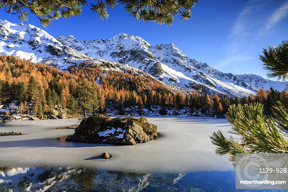 Autumn reflections at Saoseo Lake still partially frozen, Poschiavo Valley, Canton of Graubuenden, Switzerland, Europe