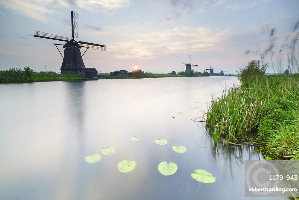 Blue sky and pink clouds on the windmills reflected in the canal at dawn, Kinderdijk, Rotterdam, South Holland, Netherlands, Europe