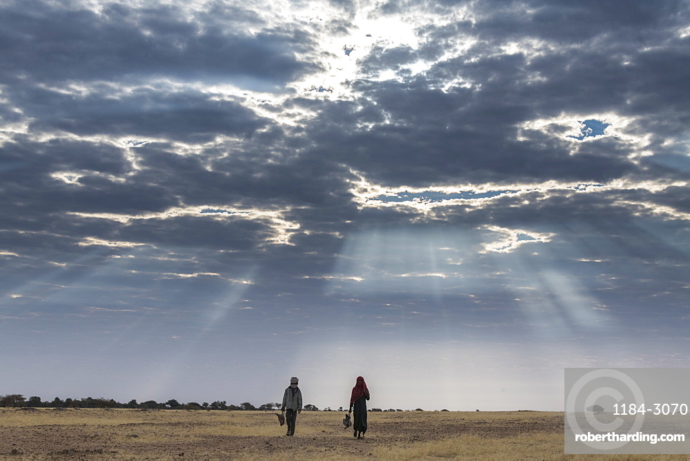 Bedouin children walking under a dramatic sky in the Sahel, Chad, Africa