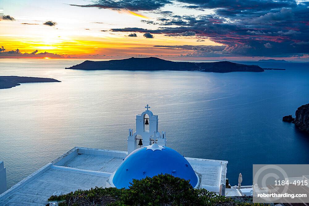 Sunset over the volcanic islands of Santorini and Anastasi Orthodox Church at sunset, Fira, Santorini, Greece