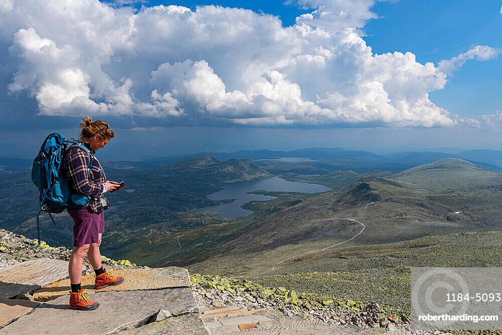 Hiker overlooking the scenery around Gausta or Gaustatoppen highest mountain in Norway, Telemark, Norway