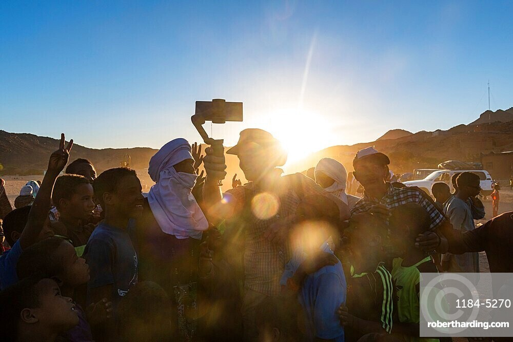 Backlight of a crowd of children and Tuareg men, Oasis Timia, Air mountains, Niger
