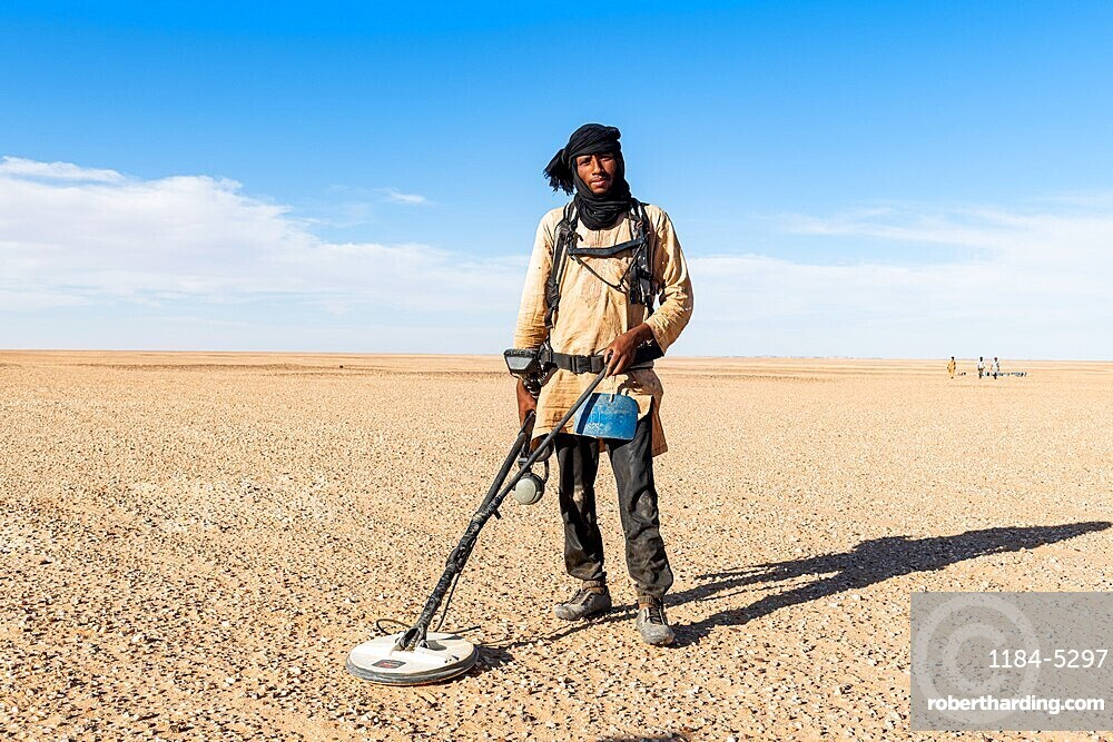 Tuareg is searching with a metal detector for gold in the Tenere desert, Niger