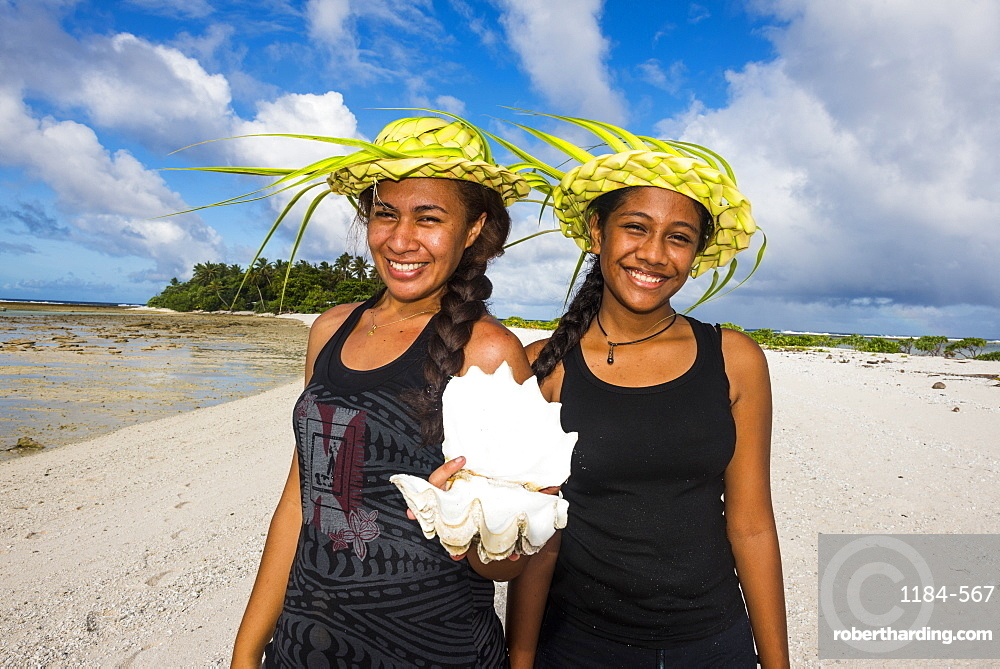 Local girls with palm leaves hats posing in the lagoon of Wallis, Wallis and Futuna, Pacific