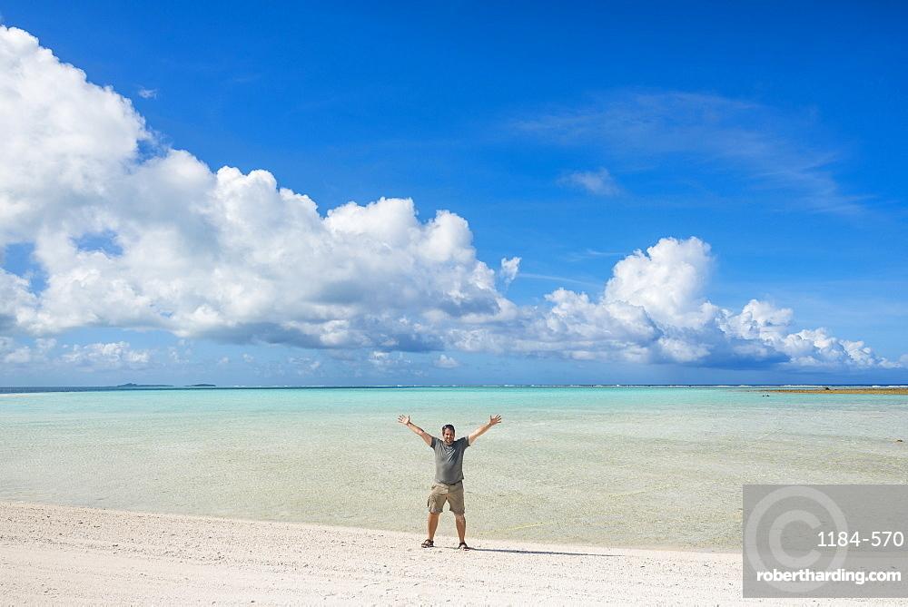 Man standing on a white sand beach in the lagoon of Wallis, Wallis and Futuna, Pacific