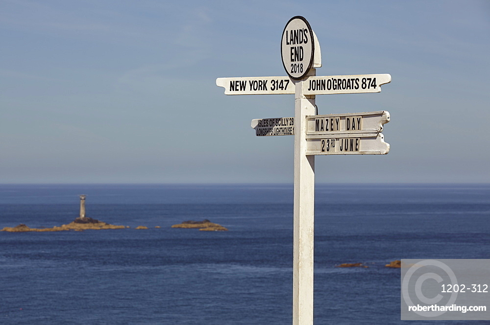 A signpost at Land's End, Britain's most southwesterly point, with Longships Lighthouse and the Atlantic Ocean behind, Cornwall, England, United Kingdom, Europe