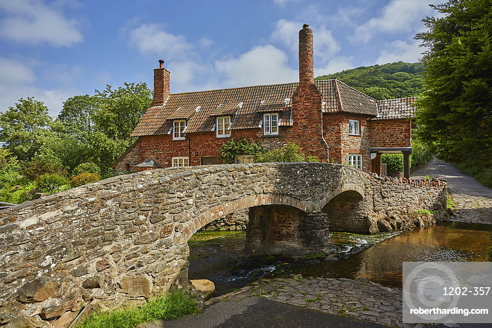 The packhorse bridge and old cottages in the village of Allerford, in Exmoor National Park, Somerset, Great Britain.