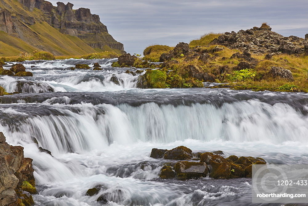 A classic Icelandic landscape, a river flowing along the base of a cliff, The Fossalar River, near Kirkjubaejarklaustur, Iceland, Polar Regions