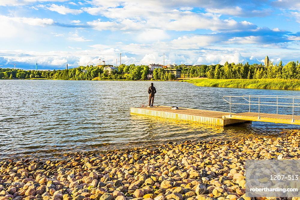 Man fishing on jetty in Toolo Bay, Helsinki, Finland, Europe