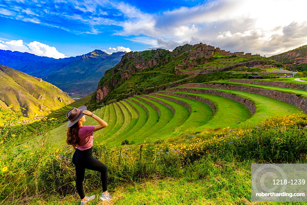 Girl gazing out at the mountain side Inca terraces at Pisac, Peru, South America