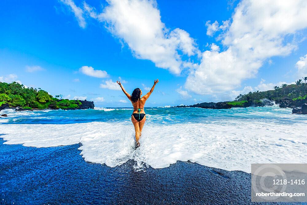 Woman enjoying the sun on one of Maui's black sand beaches, Maui, Hawaii, United States of America, North America