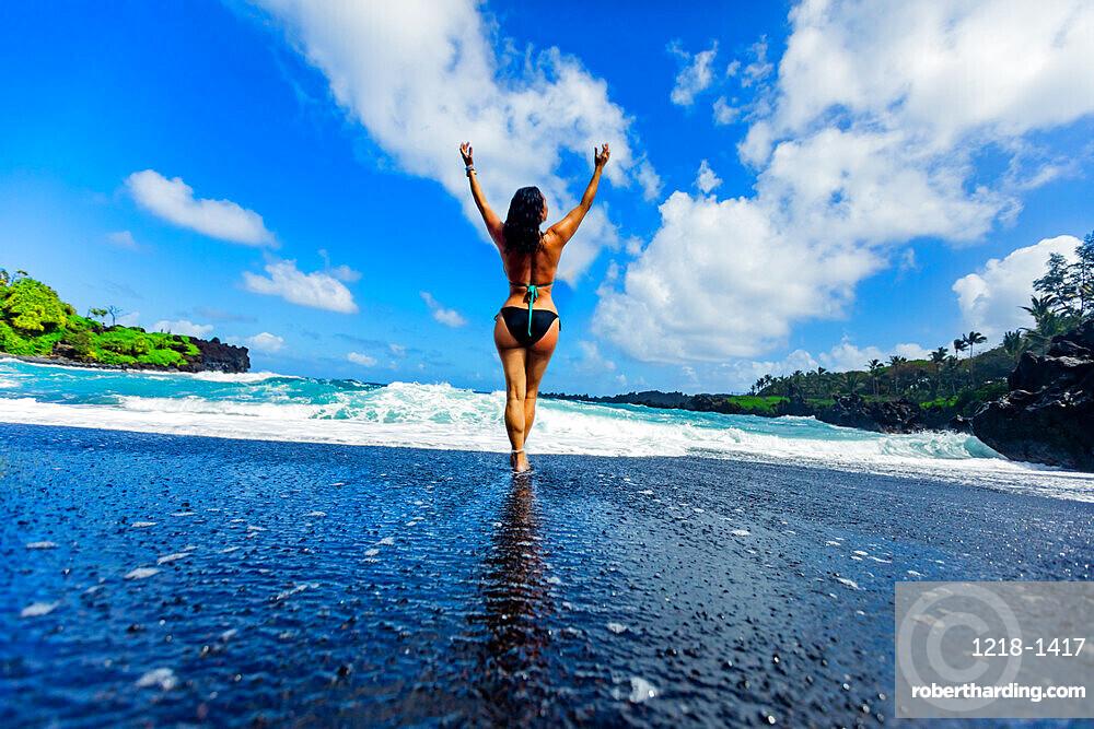 Woman enjoying the sun on one of Maui's black sand beaches, Hawaii, United States of America, North America