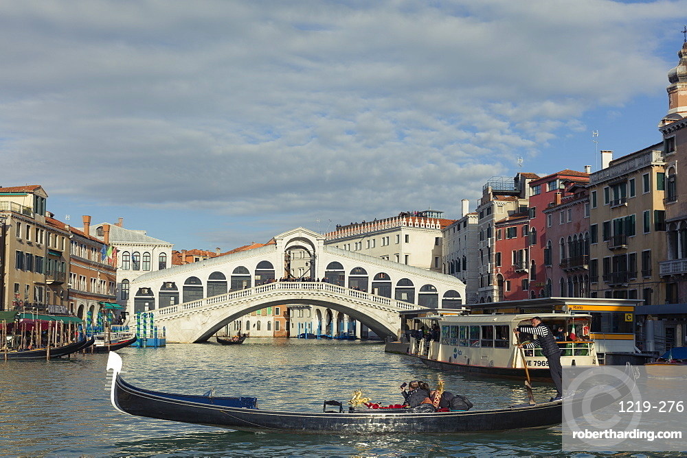A gondola crossing the Grand Canal with a vaporetto and the Rialto Bridge beyond, Venice, UNESCO World Heritage Site, Veneto, Italy, Europe