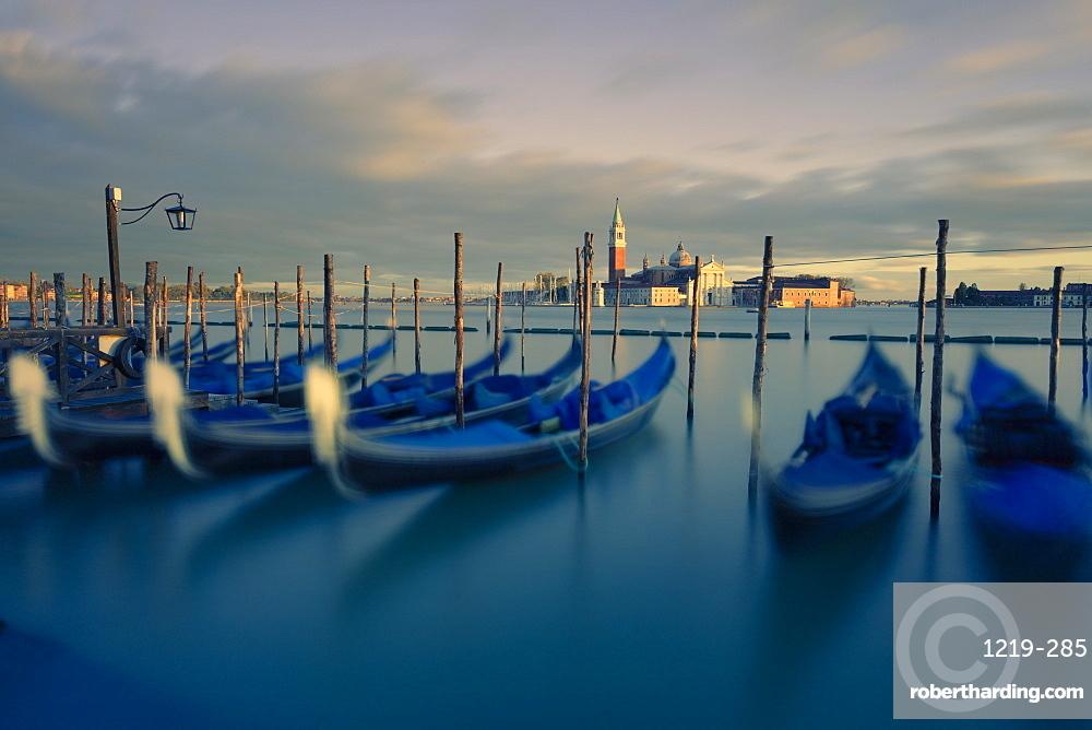 Gondolas tied to their moorings with the last light of the day illuminating San Giorgio Maggiore and its Campanile, Venice, UNESCO World Heritage Site, Veneto, Italy, Europe