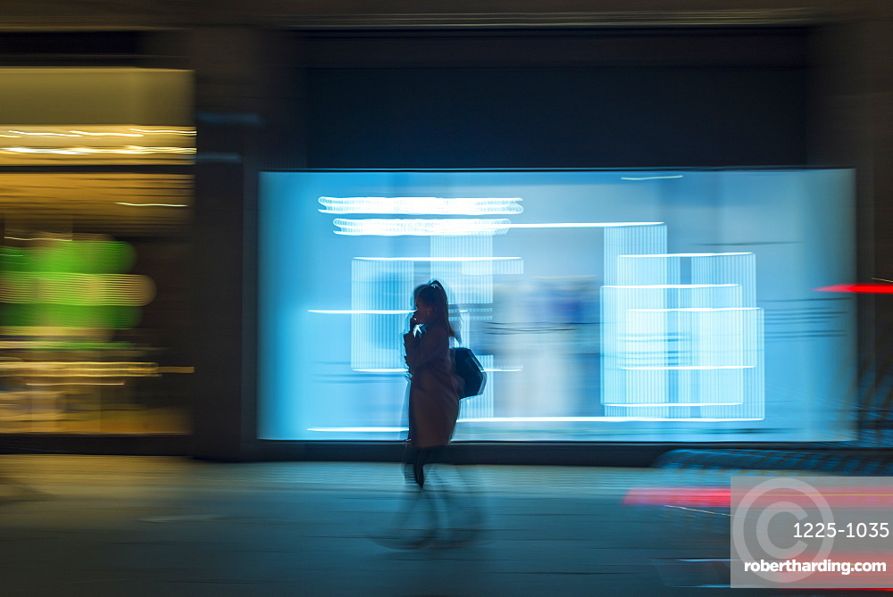 Pedestrian in a rush in the city walking at night on Oxford Street, London, England, United Kingdom, Europe