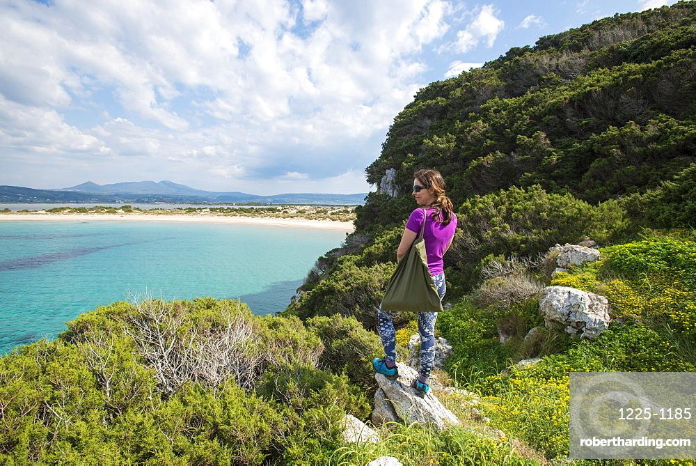 A woman explores the headland near Voidokilia Beach in the Peloponnese, Greece, Europe
