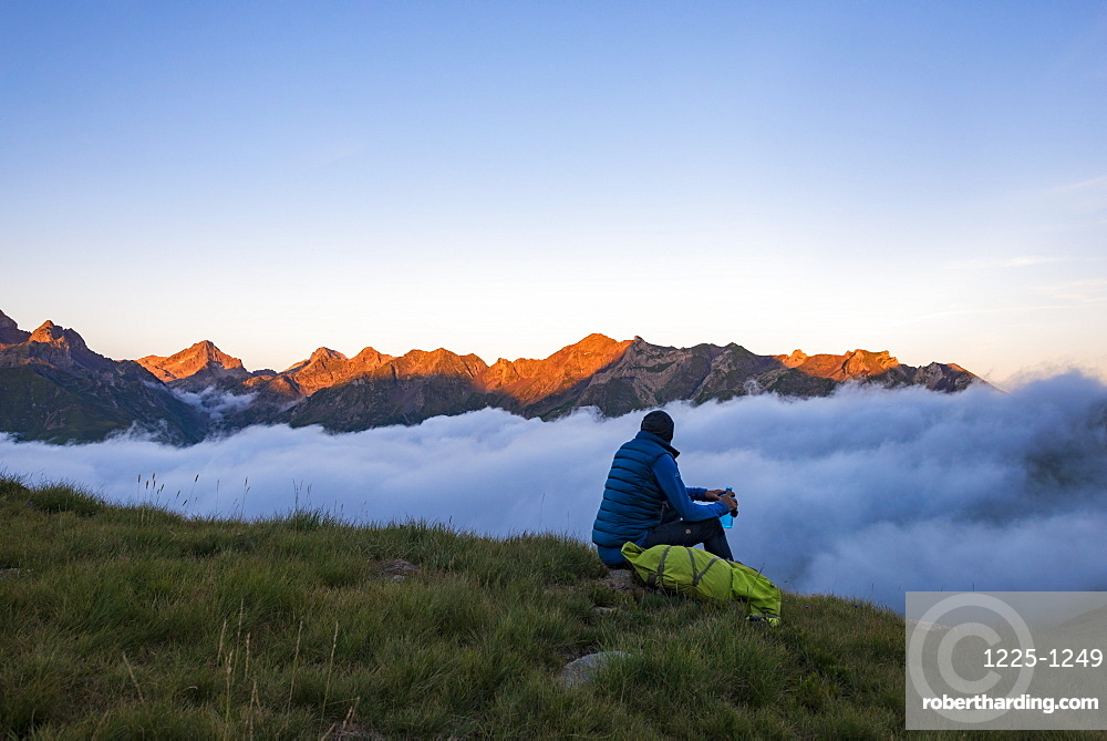 A hiker watches the sunset on the Pyrenees and a cloud inversion near Refuge Pombie along the GR10 trekking route, Pyrenees Atlantiques, France, Europe