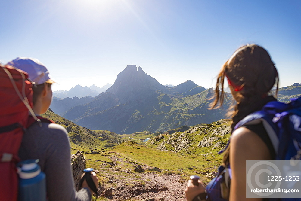 Walkers admire the view of Pic du Midi d'Ossau from the top of Col d'Ayous on the GR10 trekking route, Pyrenees Atlantiques, France, Europe