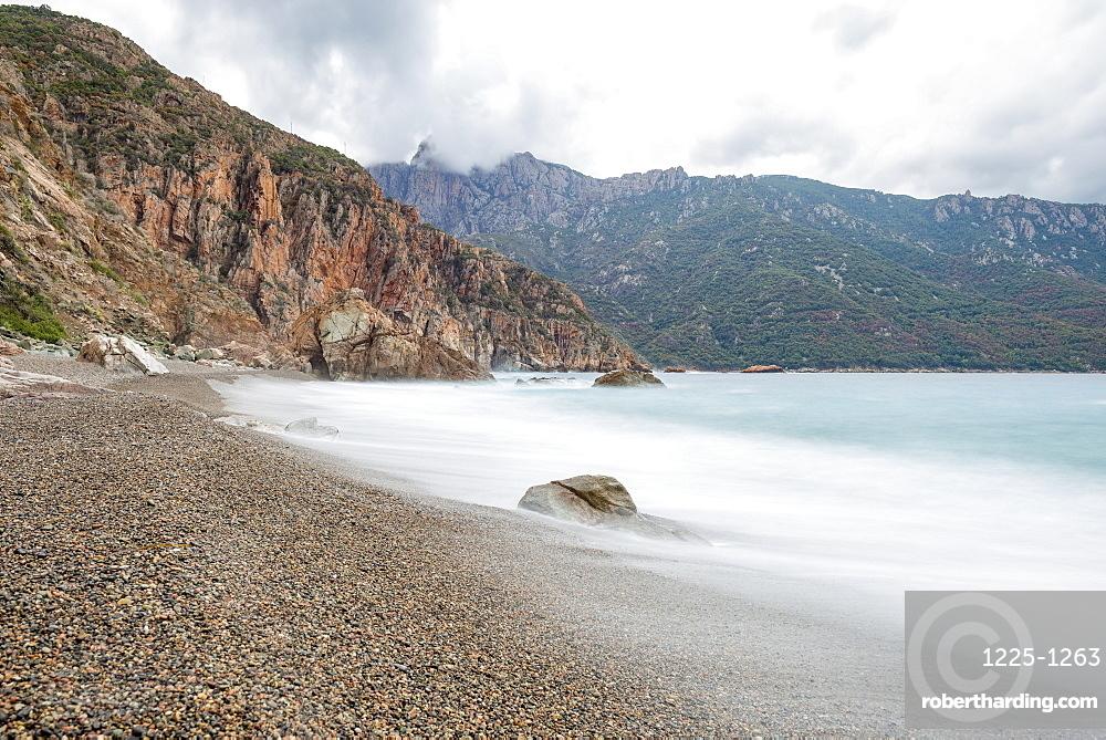 A slow exposure of waves breaking on a pebble beach in Calvi, Corsica, France, Mediterranean, Europe