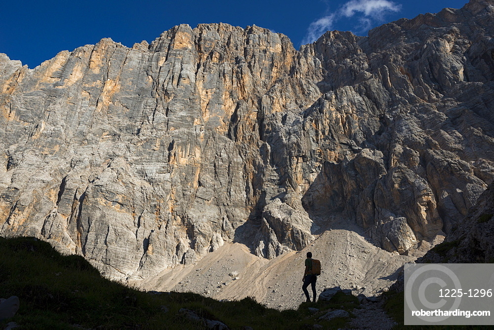 A trekker takes a break from the trail under the impressive northwest vertical wall of Monte Civetta in the Dolomites, Belluno, Veneto, Italy, Europe