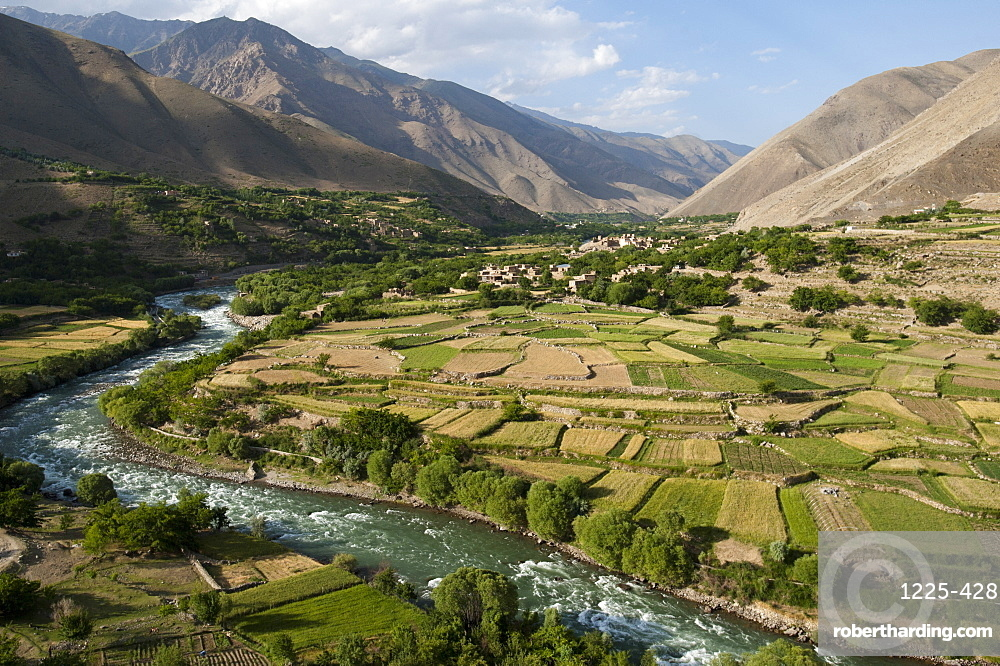 The green of the irrigated fields contrasts with the arid hills above, a testament to farmers ingenuity in this dry landscape, Afghanistan, Asia