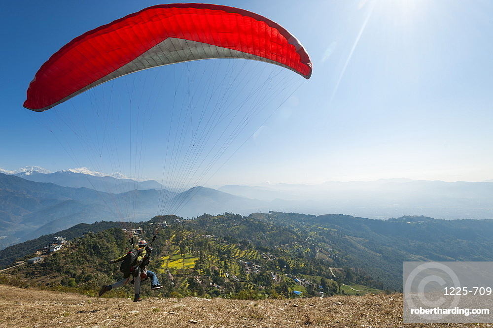 A tandem paraglider takes to the air from the top of Sarankot near Pokhara, Nepal, Himalayas, Asia