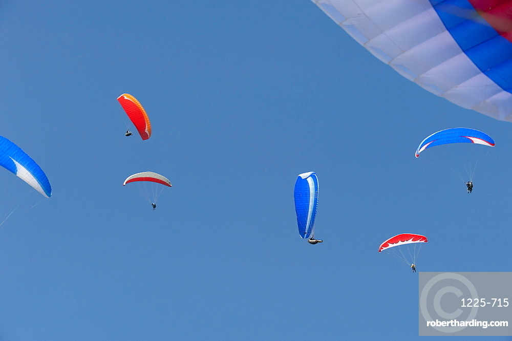 Flying on the thermals, a group of colour coordinated paragliders above Pokhara, Nepal, Asia