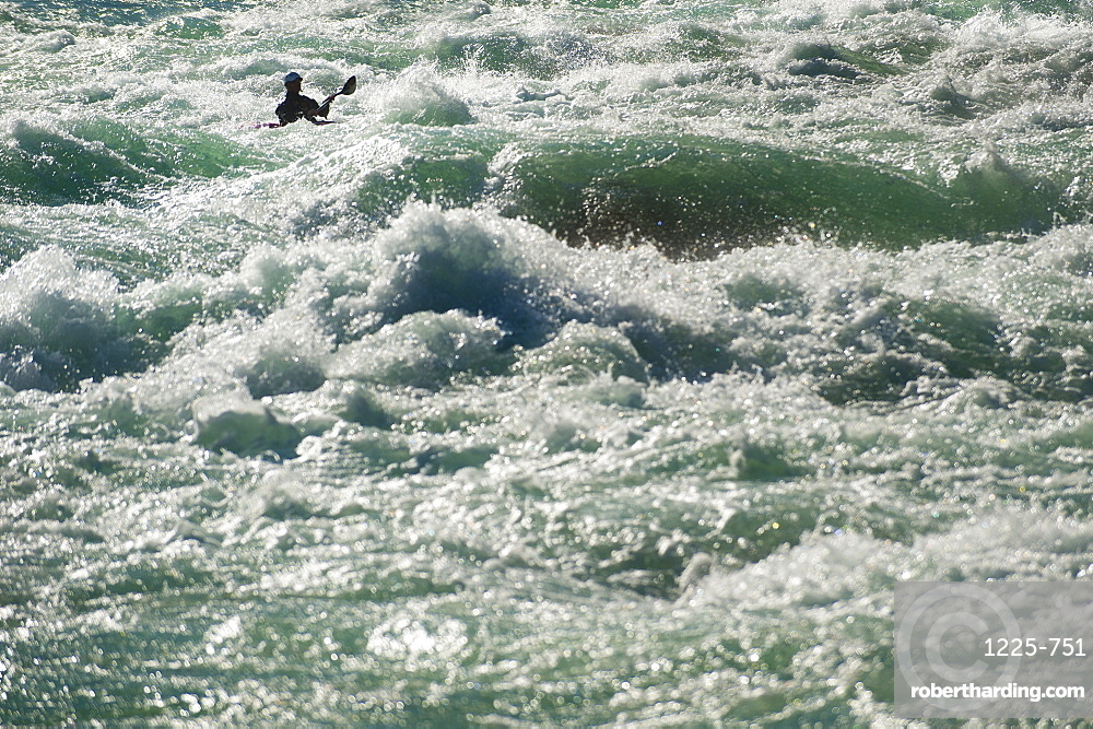 A kayaker negotiates his way through the rapids on the Karnali River in west Nepal, Asia