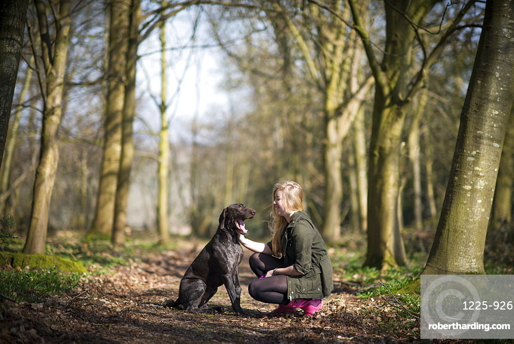 A girl takes her German short-haired pointer for a walk in woods near Ashmore in Dorset, England, United Kingdom, Europe