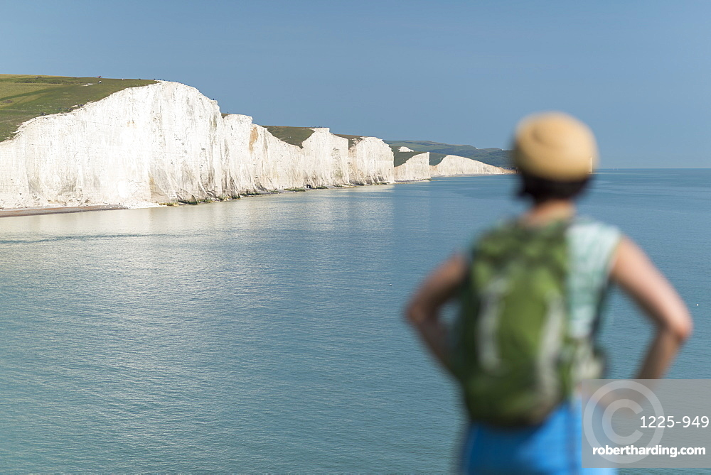 A woman looks towards the Seven Sisters while walking the South Downs Way, South Downs National Park, East Sussex, England, United Kingdom, Europe