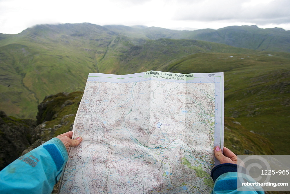 A woman checks her map while looking towards Great Langdale valley from the Langdale Pikes, Lake District, Cumbria, England, United Kingdom, Europe