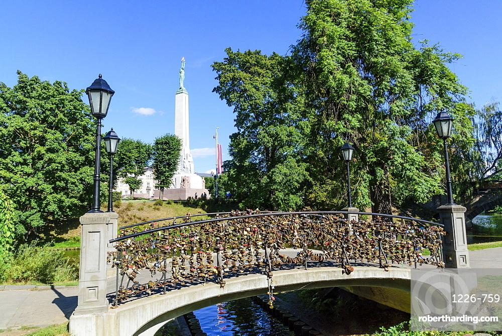 Freedom Monument and bridge with love lockets, Bastejkalna Parks, Riga, Latvia, Europe
