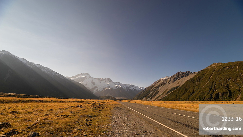 Late afternoon sun over a long straight road into the mountains, South Island, New Zealand, Pacific