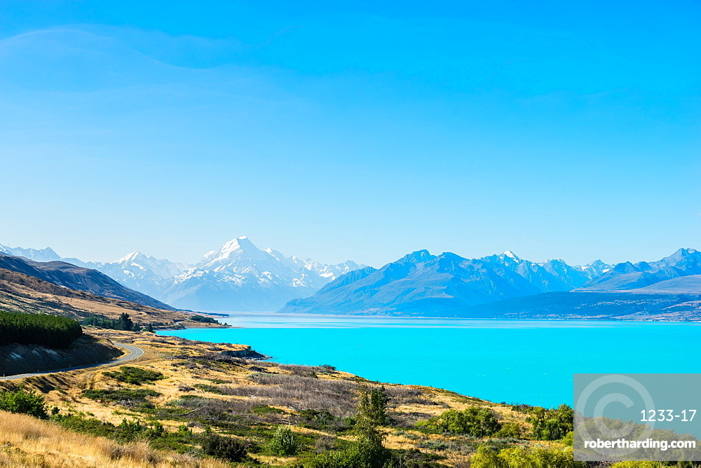 A road winds along the edge of a turquoise blue lake with mountains in the distance, South Island, New Zealand, Pacific