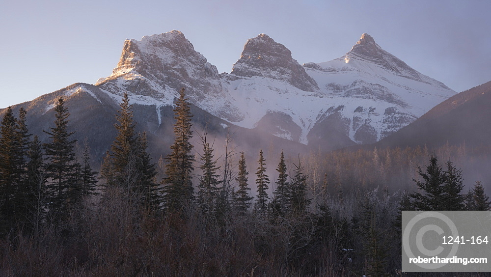 The Peaks of Three Sisters at sunrise in winter with mountain mist, Canmore, Alberta, Canadian Rockies, Canada, North America
